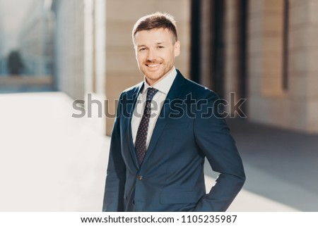Intelligent male worker wears elegant suit with tie, has pleasant talk with colleague via smart phon Stock photo © vkstudio