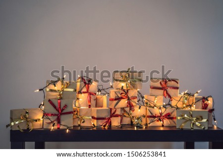 Many gifts on a black wooden table for any holiday. Present wrapped in craft paper with a red and go Stock photo © galitskaya