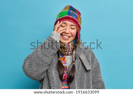 Image of girl wearing hat and scarf smiling and keeping fingers  Stock photo © deandrobot