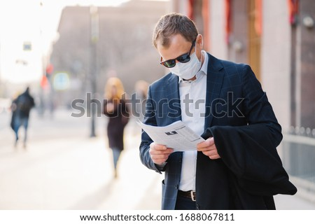 Coronavirus disease. Serious male banker reads newspaper attentively, finds out news about pandemic  Stock photo © vkstudio