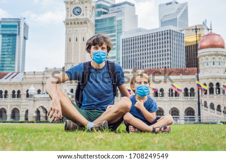 Father and son travelers in medical mask in malaysia with malaysia flag celebrating the Malaysia ind Stock photo © galitskaya