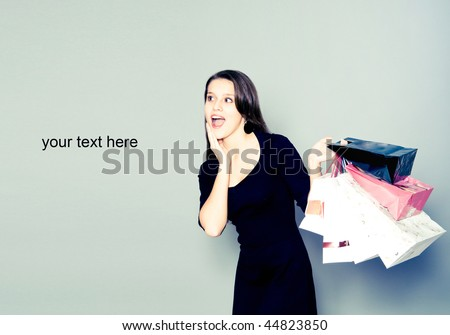 Image of astonished cute woman with shopping bags looking aside Stock photo © deandrobot