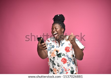 Image of excited cute woman using cellphone and expressing surprise Stock photo © deandrobot