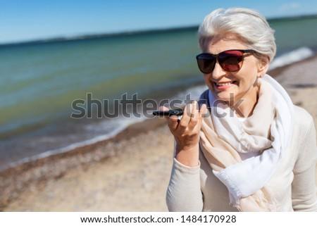 Oude vrouw stem smartphone strand oude mensen recreatie Stockfoto © dolgachov