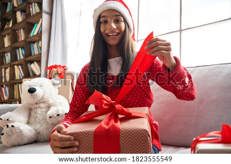 Cute girl opening christmas gift with parents in the background Stock photo © get4net