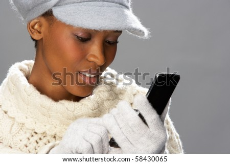 Fashionable Woman Wearing Knitwear And Cap In Studio Using Mobil Stock photo © monkey_business