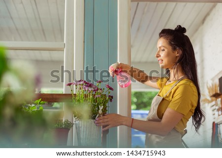 concentrated pretty young woman gardener taking care of plants stock photo © deandrobot