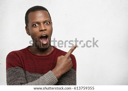 Amazing young african man dressed in shirt pointing to camera Stock photo © deandrobot