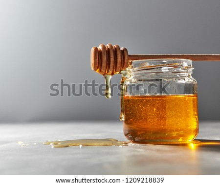 Organic sweet flower hohey dripping from stick into glass pot on a gray table. Rosh hashanah jewish  Stock photo © artjazz
