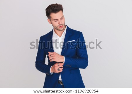 portrait of gentleman arranging cuffs and looking down to side Stock photo © feedough