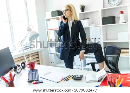 Stock photo: A young girl in glasses stands near a table, talks on the phone and draws a marker on a magnetic boa