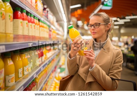 pretty young woman shopping for her favorite fruit juicesmooth stock photo © lightpoet