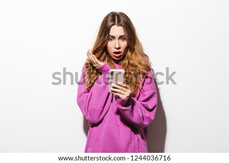 Portrait of puzzled woman 20s wearing sweatshirt using smartphon Stock photo © deandrobot
