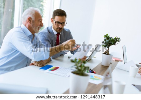 senior and young businessmen using a laptop examining documen stock photo © boggy