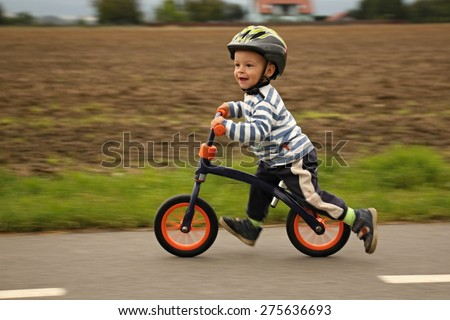 Little boy on a bicycle. Caught in motion, on a driveway. Preschool child's first day on the bike. T Stock photo © galitskaya