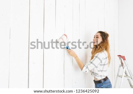 Image of amusing woman 20s painting white wall and making renova Stock photo © deandrobot
