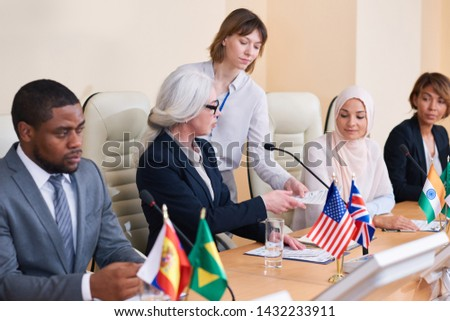 Young secretary giving documents to one of intercultural delegates Stock photo © pressmaster