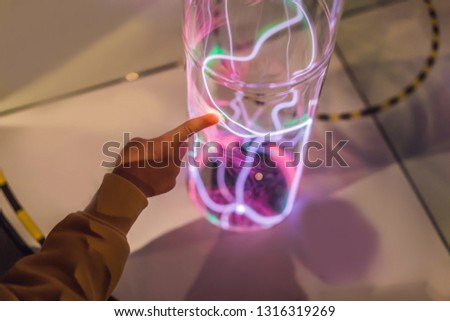 Hand of a boytauching the tube with glowing gas. inert gas light emission. tube with a glowing plasm Stock photo © galitskaya