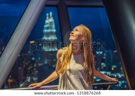 Woman looks at Kuala lumpur cityscape. Panoramic view of Kuala Lumpur city skyline evening at sunset Stock photo © galitskaya