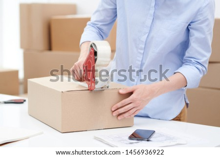 Young female sticking packed order of client with adhesive tape Stock photo © pressmaster