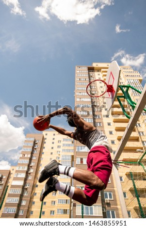 View from below of young African basketballer in jump throwing ball in basket Stock photo © pressmaster