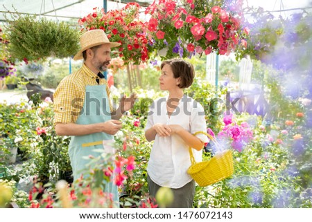 confident male gardener consulting one of buyers of his flowers stock photo © pressmaster