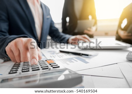 Business team using a calculator to calculate the numbers on his Stock photo © Freedomz