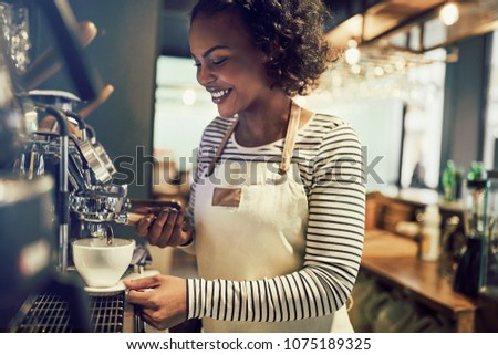 Young barista standing by coffee machine while preparing drinks for clients Stock photo © pressmaster