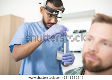 Young serious doctor in gloves putting medical stick into flask before treatment Stock photo © pressmaster