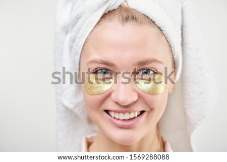 Cheerful girl with towel on head and revitalising golden under-eye patches Stock photo © pressmaster