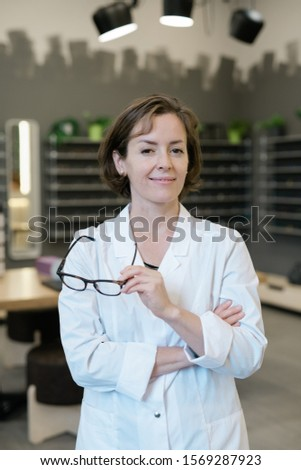 Pretty young clinician holding pair of new eyeglasses in optics shop Stock photo © pressmaster