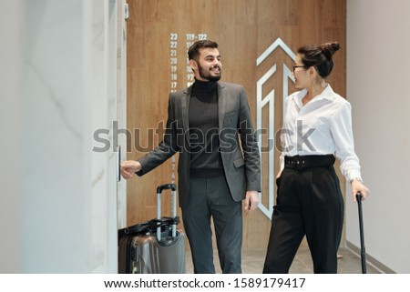 Intercultural business travelers interacting by one of elevator doors in hotel Stock photo © pressmaster