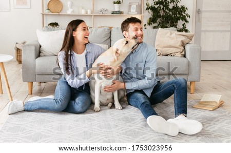 Positive young husband and wife play with dog, sit on cardboard boxes, drink takeaway coffee, have b Stock photo © vkstudio