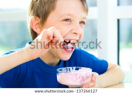 Happy young boy eating a tasty ice cream or frozen yogurt BANNER, LONG FORMAT Stock photo © galitskaya