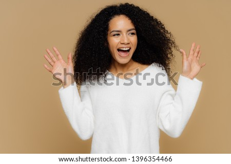 Glad overemotive woman surprised by pleasant relevation, raises hands and shows palms, focused aside Stock photo © vkstudio