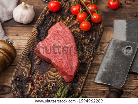 Slice of Raw Beef Topside Joint with Salt and Pepper on round chopping board with fork and knife, as Stock photo © DenisMArt