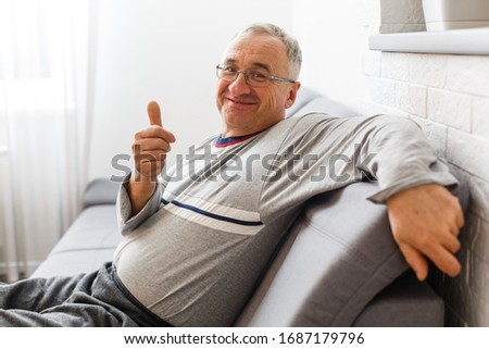 Front view of thoughtful senior Caucasian male patient sitting on bed at retirement home Stock photo © wavebreak_media