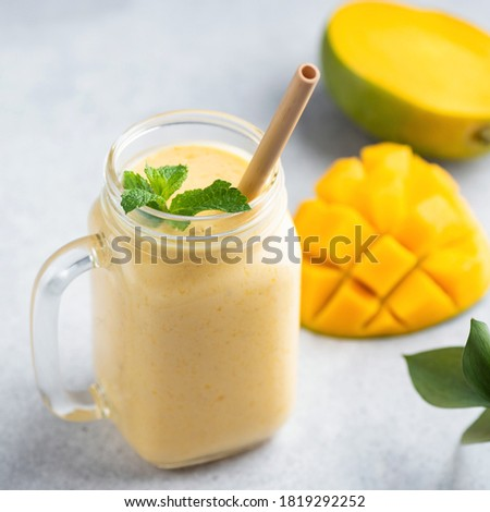 Glass of mango smoothie with bamboo drinking straw. Exotic vacation, chill out drink concept Stock photo © galitskaya