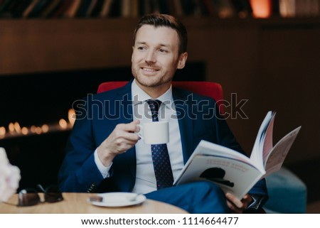Cheerful unshaven male manager or employee has pleased expression, holds cup of coffee, rests in caf Stock photo © vkstudio