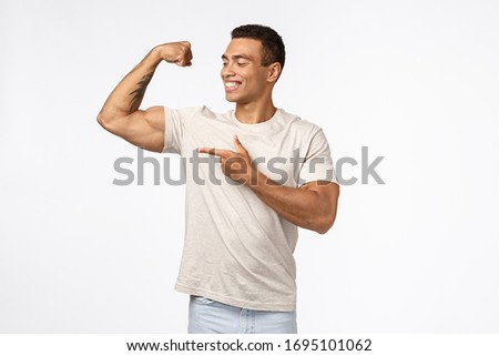 Satisfied, proud assertive young brazilian man with strong muscles, tense raised arm, smiling and po Stock photo © benzoix