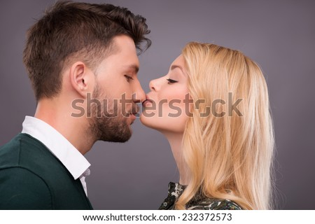 smiling young man embracing his pretty girlfriend wearing hay ha stock photo © hasloo