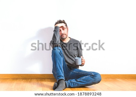 handsome young man sitting on floor in his apartment stock photo © zurijeta