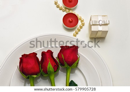 Red Roses on a white plate, candles and giftbox. Romantic composition for Valentine's Day, Anniversa Stock photo © frimufilms