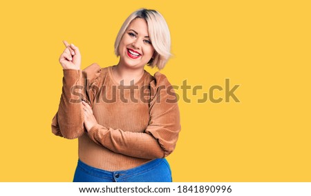Emotional smiling happy plus size model standing in studio looking in camera offering mobile phone t Stock photo © Traimak