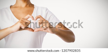 Smiling women making heart shape with their fingers around pink ribbon on a white backgroud Stock photo © wavebreak_media
