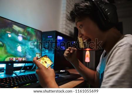 Asya erkek çığlık atan oynama video oyunları Stok fotoğraf © deandrobot
