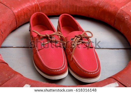 Red boat shoes on wooden background near lifebuoy. Top view. Close up stock photo © Illia