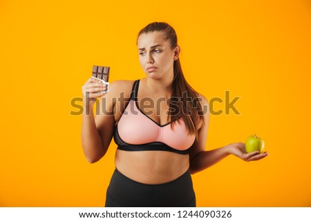 Image of young chubby woman in tracksuit holding apple and crois Stock photo © deandrobot