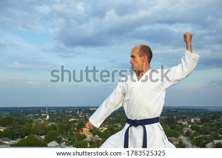 Sportsman performs formal exercises of karate on a blue background Stock photo © Andreyfire
