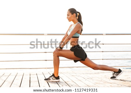 Photo of feminine sportswoman 20s in tracksuit stretching her ar Stock photo © deandrobot